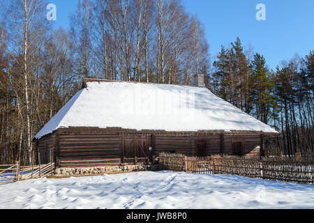 Traditional wooden barn, baltic and scandinavian style. Winter scene in the countryside. - Stock Photo