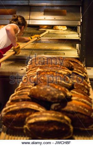 An artisan baker positions freshly made bread inside an industrial oven. - Stock Photo