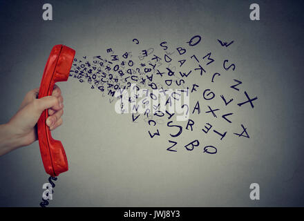 Hand holding telephone handset with alphabet letters coming out. Too many words during conversation concept - Stock Photo