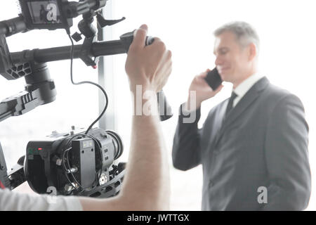 Videographer using steadycam, making video of businessman talking on phone - Stock Photo