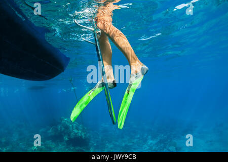 Child in snorkelling fins stand on divers boat ladder for diving underwater in tropical coral reef sea pool. Travel - Stock Photo
