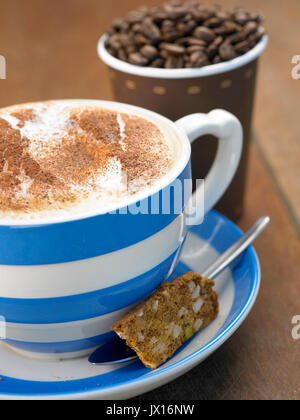 cappuccino coffee in large blue and white mug with cinnamon with takeaway cup full of beans ,newspaper and biscotti - Stock Photo