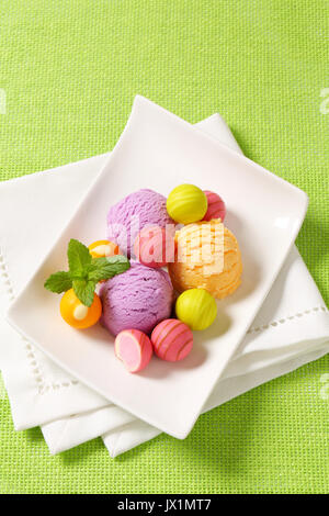 Fruit-flavored ice cream and white chocolate bonbons with fruit ganache filling - Stock Photo