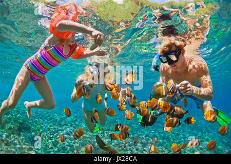 Happy family - father, mother, child in snorkeling mask dive underwater with fishes in coral reef sea pool. Travel - Stock Photo