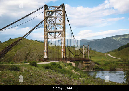 wooden suspension bridge over a mountain river high in the mountains of Altai. - Stock Photo