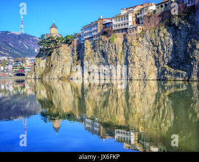 Metekhi Church and traditional houses on a steep rock reflecting in Kura River, Tbilisi Old Town, Georgia - Stock Photo