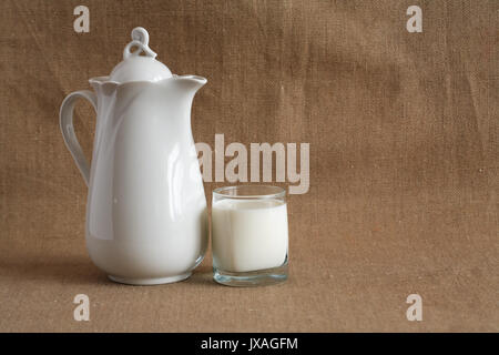 Glass full of milk near pitcher on canvas background - Stock Photo