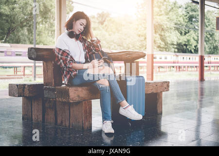 Traveler girl using tablet with a luggage sitting and waiting for train on the station. Outdoor adventure travel - Stock Photo