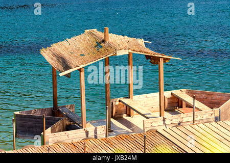 Boat bridge with simple boat house or wooden boat with thatched roof. - Stock Photo