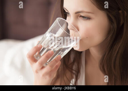 Young dehydrated woman feeling thirsty, drinking mineral water f - Stock Photo