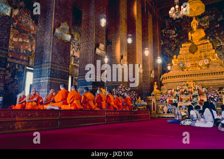 BANGKOK, THAILAND- DECEMBER 26, 2016: Buddhist monks pray at Wat Pho temple in Thailand's capital, Bangkok. - Stock Photo