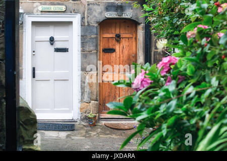 Two doors to a closed cottage in England. One white and the other brown. - Stock Photo