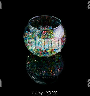 Colored hydrogel balls in a glass vase isolated on a black background - Stock Photo
