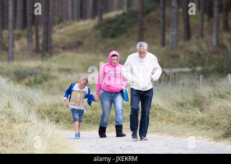 Walkers walking along forest path at Newborough Forest during a cool and windy summers day, Anglesey, Wales, UK - Stock Photo