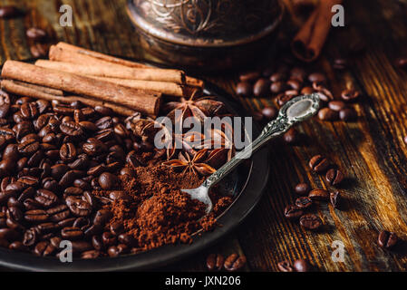 Coffee Beans with Spooonful of Ground Coffee, Cinnamon Sticks and Chinese Star Anise on Metal Plate. Some Beans - Stock Photo