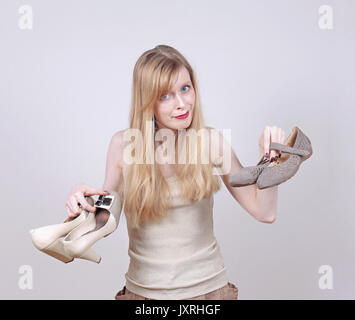 Young woman showing comfortable flat shoes after taking off high heals - Stock Photo