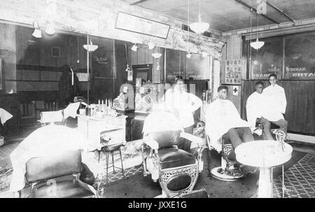Two African American men sit in barber chairs, each with an African American barbers standing by, in a barbershop - Stock Photo