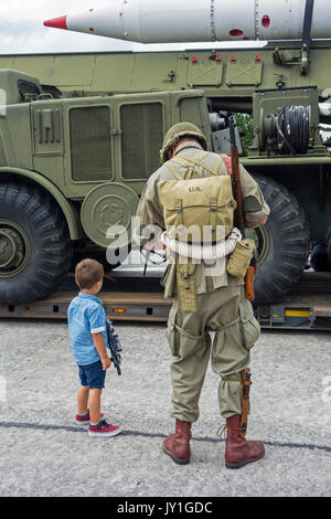 Little boy with toy gun and WW2 reenactor in US soldier outfit looking at missile truck at World War Two militaria - Stock Photo