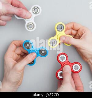 Hands holding popular fidget spinner toy - Stock Photo