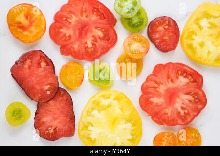 Lycopersicon esculentum. Slices of brightly coloured heritage tomatoes. - Stock Photo