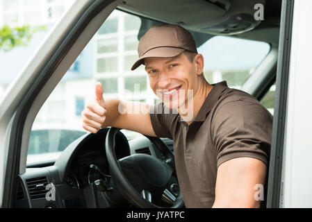 Young Happy Deliverymen Showing Thumb Up Sign In Van - Stock Photo