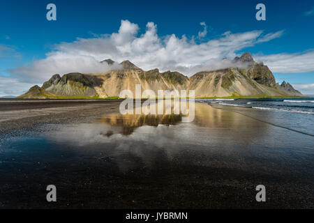 Vestrahorn reflections in the wet beach. - Stock Photo