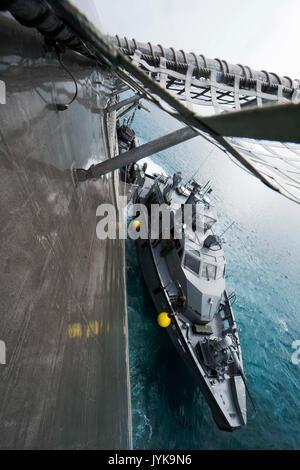 A MK VI patrol boat, assigned to Coastal Riverine Group-1, pulls alongside the littoral combat ship USS Coronado - Stock Photo