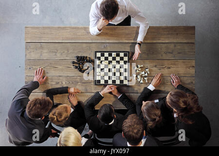 Business people playing chess, team of workers losing, leader is winning - Stock Photo