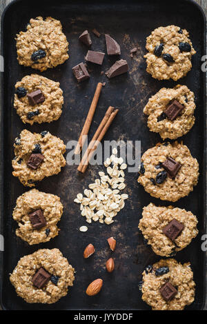 Top view of freshly baked oatmeal raisin cookies with dark chocolate, cinnamon and nuts on old rusty cookies sheet. - Stock Photo