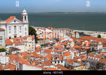 Terracotta roofs and the ancient church seen from Miradouro Alfama one of the many viewpoints of Lisbon Portugal - Stock Photo