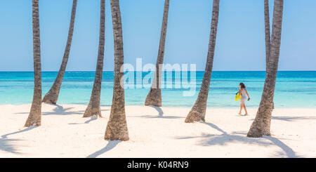 Juanillo Beach (playa Juanillo), Punta Cana, Dominican Republic. Woman walking on the palm-fringed beach (MR). - Stock Photo