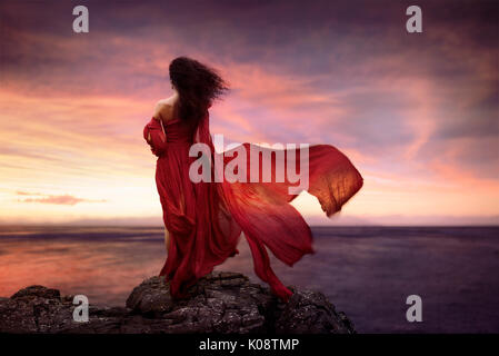 Beautiful artistic portrait of a young woman in red long summer dress flying in the wind standing on a rocky shore - Stock Photo