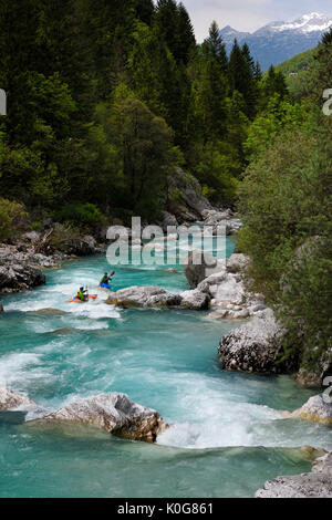 Kayakers paddling the cold emerald green alpine water of the Upper Soca River near Bovec Slovenia with Kanin mountains - Stock Photo
