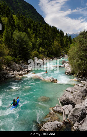 Kayakers shooting the cold emerald green alpine water of the Upper Soca River near Bovec Slovenia with Kanin mountains - Stock Photo