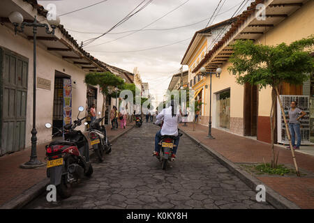 July 10, 2017 Buga, Valle de Cauca, Colombia: people riding a motorbike through the colonial downtown of the popular - Stock Photo
