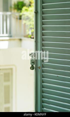 Open green wooden shutters with view on neighborhood balcony - Stock Photo