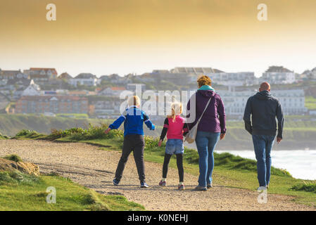 A family of holidaymakers enjoying a bracing walk in windy condition. - Stock Photo