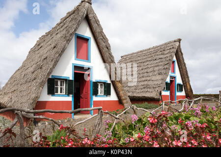Old traditional Madeira huts famous for the characteristic triangle thatched roofs in Santana, Madeira Portugal. - Stock Photo