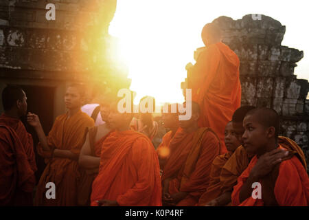 SIEM REAP, CAMBODIA - MAY 2, 2010: Unidentified young monks at Bayon ruin temple at sunset. - Stock Photo