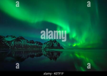 Aurora reflections on Stokksnes black beach over Vestrahorn mountains, Iceland - Stock Photo