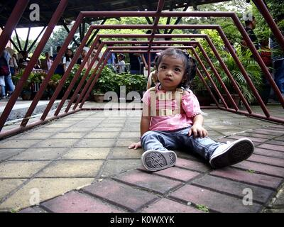 QUEZON CITY, PHILIPPINES - AUGUST 16, 2017: A little girl playing under a bicycle parking rack. - Stock Photo