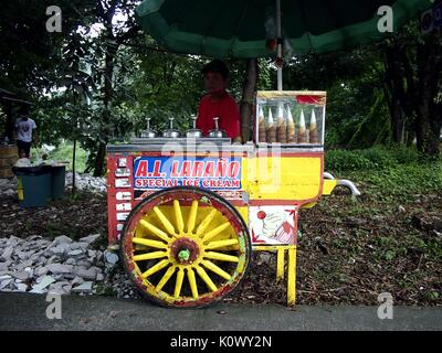 QUEZON CITY, PHILIPPINES - AUGUST 16, 2017: An ice cream vendor with his food cart at a sidewalk waiting for customers. - Stock Photo
