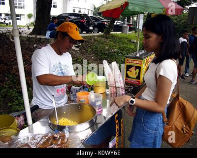 QUEZON CITY, PHILIPPINES - AUGUST 16, 2017: A street food vendor serves sweet corn to a customer. - Stock Photo