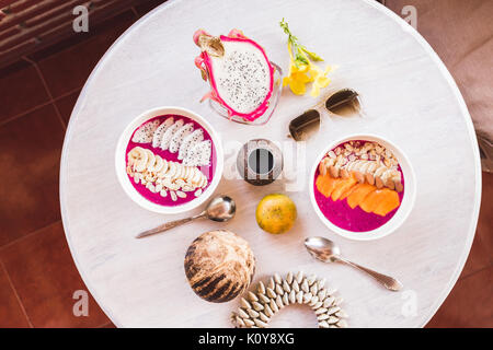 Healthy and tasty fresh breakfast on vintage round table served with sliced mango and dragon fruit, fresh papaya, - Stock Photo