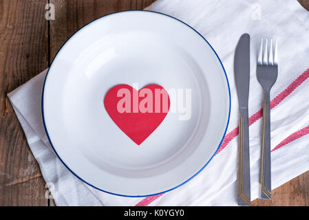 Concept diet and weight loss. Empty plate with red paper heart in the middle of the plate - Stock Photo