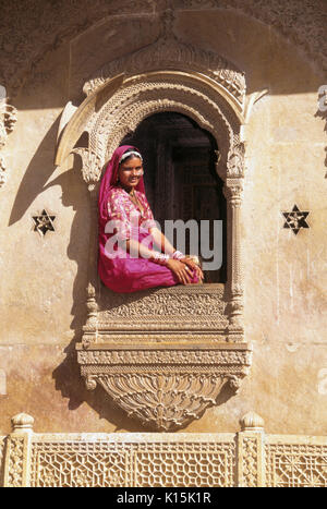 Woman sitting in window of Patwon-ki-Haveli (House of the Brocade Merchants), Jaisalmer, Rajasthan, India - Stock Photo