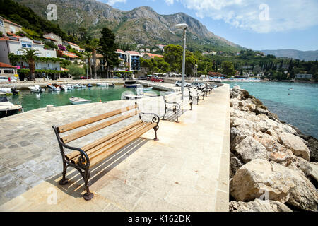 A row of benches on pier at Dubrovnik riviera in Mlini, Croatia. - Stock Photo