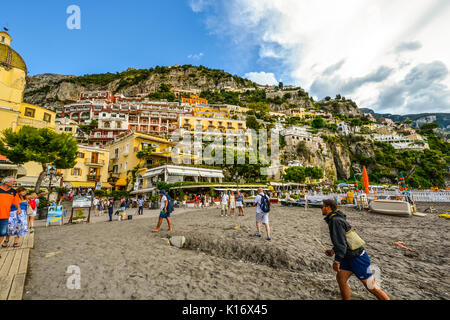 Summer day at the sandy beach of Positano Italy on the Amalfi Coast as tourists enjoy the coastal cafes and shops - Stock Photo