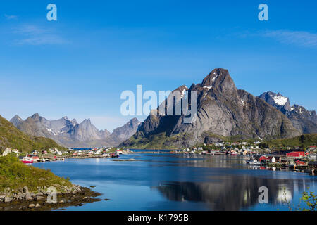 View across scenic natural fishing harbour to mountains in summer. Reine, Moskenes, Moskenesøya Island, Lofoten - Stock Photo