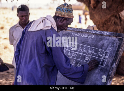 Niger, Doutouel Village, West Africa.  Man Practicing Writing in Adult Literacy Class. - Stock Photo